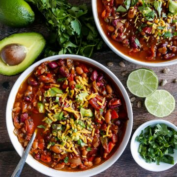 two bowls of vegetarian chili with cilantro lime and avocado scattered on table