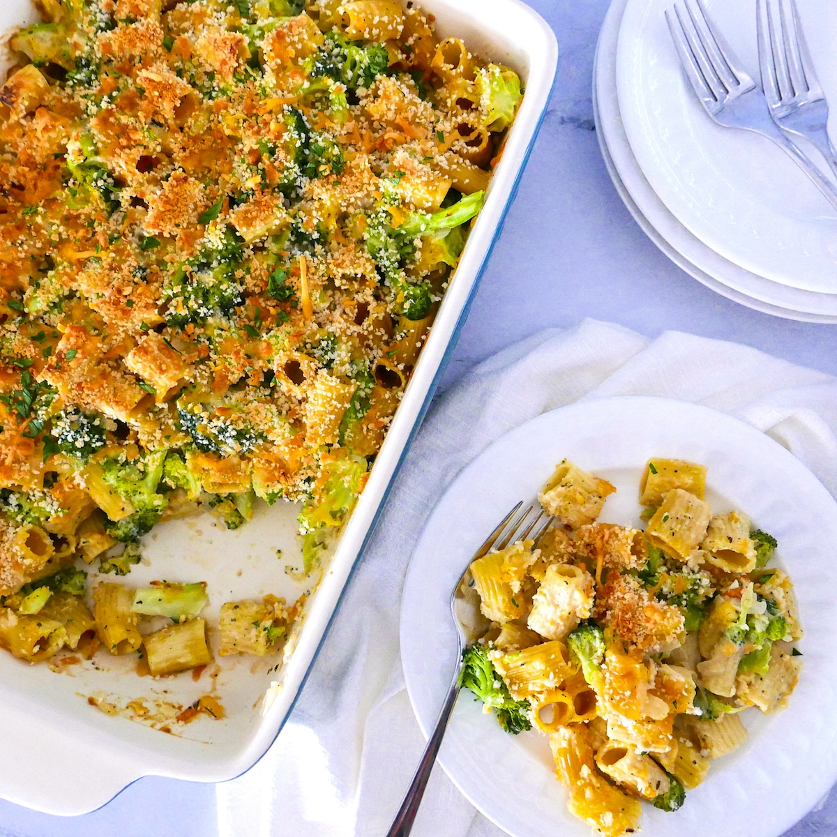 broccoli pasta bake on a white plate and in a baking dish with two forks and white napkin